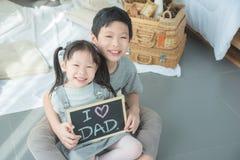 Enfants asiatiques souriant tout en tenant le tableau noir Photos libres de droits