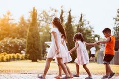 Enfants asiatiques tenant la main et marchant ensemble en parc Image libre de droits