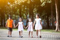 Enfants asiatiques tenant la main et marchant ensemble en parc Photo libre de droits