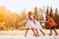 Enfants asiatiques tenant la main et marchant ensemble en parc Photos stock