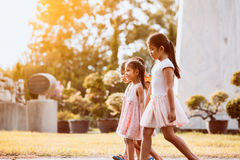 Enfants asiatiques tenant la main et marchant ensemble en parc Images stock