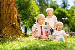 Enfants attentifs lisant un livre en parc image libre de droits