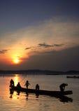 Enfants au bateau sur le coucher du soleil Photographie stock