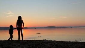 Enfants aux cailloux de jet de coucher du soleil dans la mer HD 1920x1080 banque de vidéos