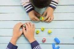 Enfants avec de l'argile et créativité d'utilisation pour faire le fruit et etc. La vue supérieure et bourdonnent dedans images libres de droits