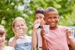Enfants avec de l'eau potable de tasses en plastique Photographie stock