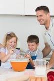 Enfants avec des biscuits de cuisson de père au plan de travail Photos stock