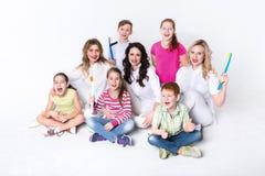 Enfants avec des brosses à dents et des médecins sur le blanc Images stock