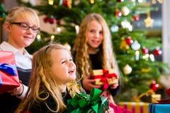 Enfants avec des cadeaux de Noël le jour de Noël Images stock