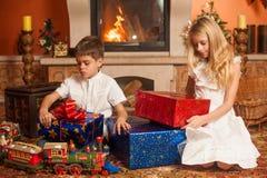 Enfants avec des cadeaux par la cheminée Photographie stock libre de droits