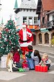 Enfants avec des cadeaux regardant Santa Claus Images libres de droits