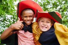 Enfants avec des costumes tenant des pouces  Photos libres de droits