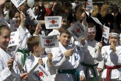 Enfants avec des drapeaux supportant le Japon Image libre de droits