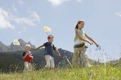 Enfants avec des filets de papillon marchant par le champ Photo libre de droits