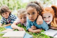 Enfants avec des livres se trouvant sur l'herbe Photo stock