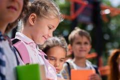 Enfants avec des livres sur le terrain de jeu Images stock