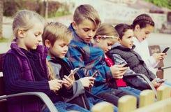 Enfants avec des périphériques mobiles Photos stock