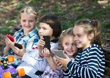 Enfants avec des périphériques mobiles extérieurs Photo libre de droits