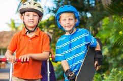 Enfants avec des panneaux et des scooters de patin Photographie stock libre de droits