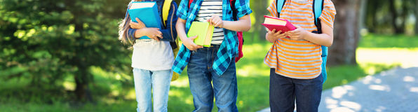 Enfants avec des sacs à dos se tenant en parc près de l'école Photos stock