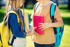 Enfants avec des sacs à dos se tenant en parc près de l'école Photos libres de droits