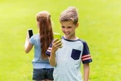 Enfants avec des smartphones jouant le jeu en parc d'été Photos stock