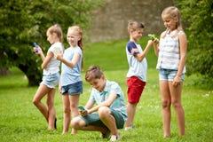 Enfants avec des smartphones jouant le jeu en parc d'été Images libres de droits