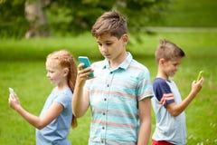 Enfants avec des smartphones jouant le jeu en parc d'été Photo stock