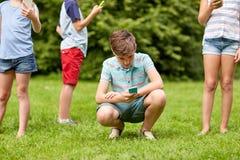 Enfants avec des smartphones jouant le jeu en parc d'été Images stock
