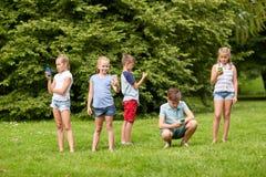 Enfants avec des smartphones jouant le jeu en parc d'été Image stock