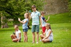 Enfants avec des smartphones jouant le jeu en parc d'été Photos libres de droits
