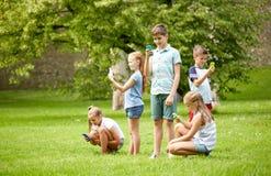 Enfants avec des smartphones jouant le jeu en parc d'été Photographie stock libre de droits