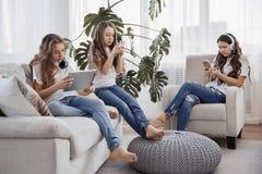 Enfants avec des téléphones et des comprimés, avec des smartphones et des écouteurs Le groupe d'adolescentes utilise des instrume Image libre de droits