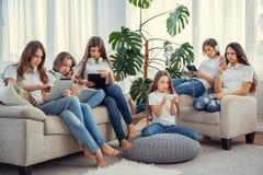 Enfants avec des téléphones et des comprimés, avec des smartphones et des écouteurs Le groupe d'adolescentes utilise des instrume Images libres de droits