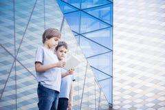 Enfants avec des tablettes dans la ville Photos libres de droits