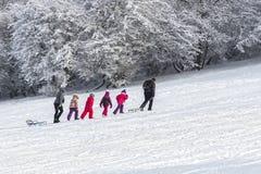 Enfants avec des traîneaux sur la neige Photo stock