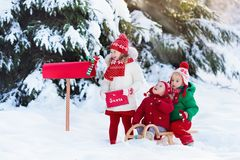 Enfants avec la lettre à Santa à la boîte aux lettres de Noël dans la neige Photos libres de droits