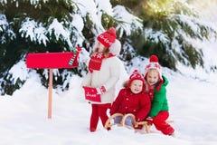 Enfants avec la lettre à Santa à la boîte aux lettres de Noël dans la neige Images stock