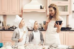 Enfants avec la mère dans la cuisine La famille lit la recette sur le comprimé images stock
