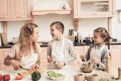 Enfants avec la mère dans la cuisine Les enfants aident la mère à faire la salade image stock