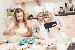 Enfants avec la mère dans la cuisine La mère met la pâte dans le plat de cuisson et les enfants regardent sur le comprimé images stock