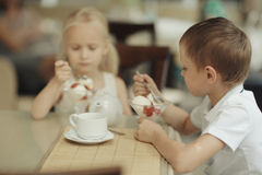Enfants avec le dessert en café Photo stock