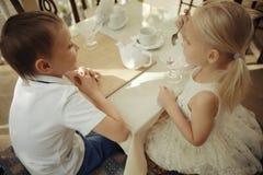 Enfants avec le dessert en café Photos stock