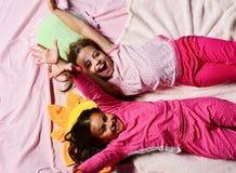 Enfants avec le mensonge gai de visages dans le lit Écolières dans des pyjamas photos libres de droits