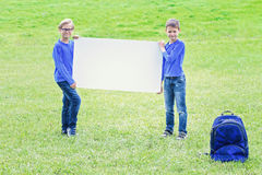 Enfants avec le panneau blanc vide de plaquette dehors Photo libre de droits