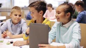 Enfants avec le PC de comprimé programmant à l'école de robotique