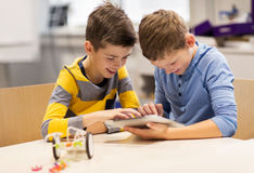 Enfants avec le PC de comprimé programmant à l'école de robotique Photo stock