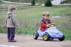 Enfants avec le véhicule de jouet à l'extérieur Photos stock