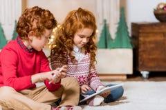 Enfants avec les dispositifs numériques Image libre de droits