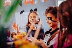 Enfants avec les visages peints se sentant amusés et stupéfaits célébrant Halloween images libres de droits